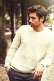 Handsome serene and pensive young man model in a trees park. Charming young and handsome man with stylish hair and white sweater. Outdoors in a park with a Stock Images