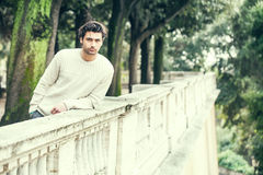 Handsome serene young man model leaning on a wall of a terrace, trees park. Charming young and handsome man with stylish hair and white sweater waiting leaning Stock Images