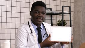 Handsome serious African doctor presenting product on tablet screen. White Display. royalty free stock photos