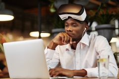 Serious african man i virtual head set, using laptop. Royalty Free Stock Images