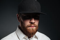 Handsome serious bearded young man wearing cap. Picture of handsome serious bearded young man wearing cap standing isolated over grey background. Looking at Stock Photos