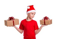 Handsome serious boy, santa hat on his head, with two gift boxes on the hands, looking to the left box. Concept royalty free stock photo