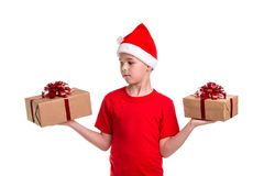 Handsome serious boy, santa hat on his head, with two gift boxes on the hands, looking to the right box. Concept royalty free stock image