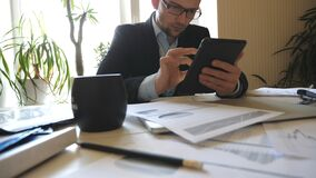 Handsome serious businessman in eyeglasses developing a business project and analysing statistical data information on a