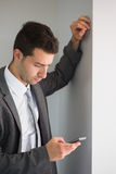 Handsome serious businessman looking at smartphone Stock Image