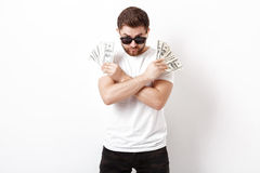 Handsome serious man with beard in shirt holding a lot of hundre Stock Images
