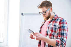 Handsome serious man with beard standing and using tablet. Handsome serious young man with beard in plaid shirt standing near flipchart and using tablet Stock Photos