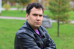 Handsome serious man in leather jacket looks at camera Stock Photos