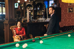 Handsome serious man playing pool. Handsome serious men playing pool,a men prepares the cue to play Billiards Royalty Free Stock Photos