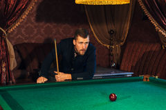 Handsome serious man playing pool. A man prepares the cue to play Billiards Royalty Free Stock Photos