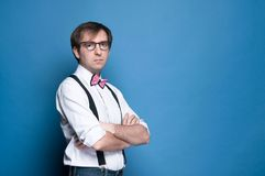 Serious man looking at camera with crossed arms on blue background with copy space royalty free stock photos