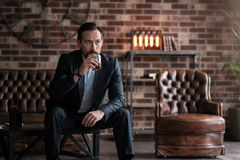 Handsome serious man taking a sip of whisky. Alcoholic beverage. Serious good looking thoughtful man sitting on the table and holding a glass while drinking Royalty Free Stock Images