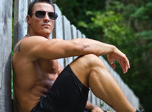 Handsome, serious muscleman sitting against wood fence Stock Image