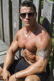 Handsome, serious muscleman sitting against wood Royalty Free Stock Photo