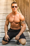 Handsome, serious muscleman sitting against wood Royalty Free Stock Image