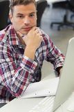 Handsome serious student using computer taking notes Stock Photography