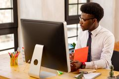 Handsome serious young businessman checking his documentation. Business strategy. Handsome serious man checking his documentation while thinking about his new royalty free stock photos