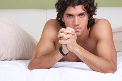 Handsome and sexy guy on sheets Stock Photo