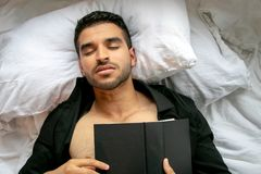 Man in bed with open shirt and pecs sleeps reading hardback book. Handsome, man in bed with open black shirt and pecs reading sleeping with hardback book stock photos