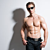 Handsome sexy man in glasses posing at studio. Royalty Free Stock Photography