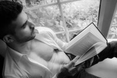 Man in sitting on window ledge with open shirt and pecs reading hardback book. Handsome, man with open white shirt and pecs reading hardback book in bay window stock images