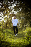 Handsome sexy man outdoors in the garden standing on fresh green grass Stock Photo