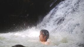 Handsome sexy man relaxing under stream water in waterfall in tropical jungle. slow motion. 1920x1080. Happy man relaxing under stream water in waterfall in stock video footage