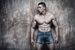 Handsome sexy muscular man, abs, on wall background Stock Photography