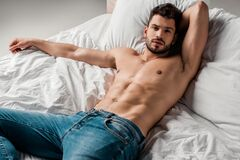 Sexy shirtless man in jeans lying