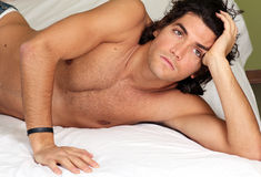 Handsome and young man on bed royalty free stock image