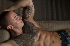 Handsome Shirtless Athletic Young Man Laying in Sofa Stock Photo
