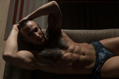 Handsome Shirtless Athletic Young Man Laying in Sofa Stock Photos