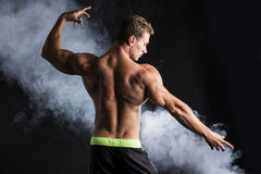 Handsome shirtless bodybuilder striking a pose, back view Stock Photos