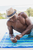 Handsome shirtless man listening to music poolside Royalty Free Stock Photos