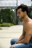 Handsome shirtless man outdoor in urban environment Royalty Free Stock Image