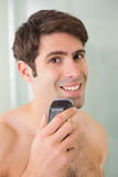 Handsome shirtless man shaving with electric razor Royalty Free Stock Photos