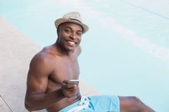 Handsome shirtless man texting on phone poolside Stock Photography