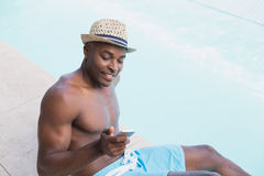 Handsome shirtless man texting on phone poolside Royalty Free Stock Photo