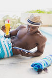 Handsome shirtless man using tablet pc poolside with cocktail Stock Photos
