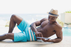 Handsome shirtless man using tablet pc poolside Royalty Free Stock Image