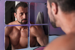 Handsome shirtless muscle man wash face in the bathroom mirror. Handsome shirtless muscle man wash face in the bathroom in mirror Stock Photo