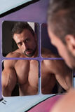 Handsome shirtless muscle man wash face in the bathroom mirror Stock Photos