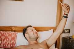 Handsome shirtless muscular bodybuilder man in jeans taking selfie with cell phone while laying on bed. young man. Handsome shirtless muscular bodybuilder man royalty free stock image
