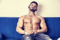 Male bodybuilder listening to music on sofa royalty free stock images