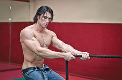 Handsome shirtless muscular man pulling rope Royalty Free Stock Photos