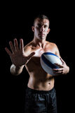 Handsome shirtless sports player showing hand while holding ball Stock Photography