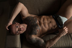 Handsome Shirtless Tattoo Young Man Laying in Bed Royalty Free Stock Photo