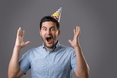 Man at party. Handsome shocked young brunet guy with party cap screaming with raised hands. New year or birthday celebration Royalty Free Stock Images