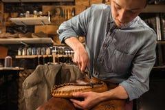 Handsome shoemaker sitting in workshop making shoes. Photo of young handsome shoemaker sitting in workshop making shoes. Looking aside stock photography