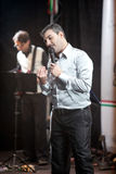 Handsome singer performing with music band Stock Photography